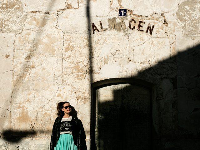 Una joven posa junto a la puerta de un almacen abandonado
